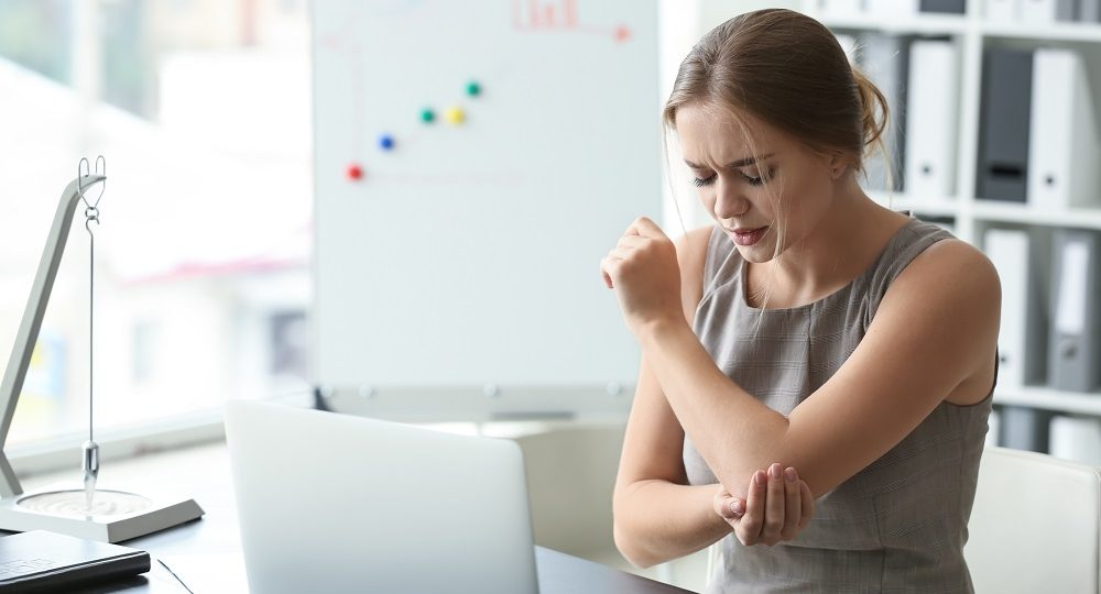 Young woman suffering from pain in elbow at workplace