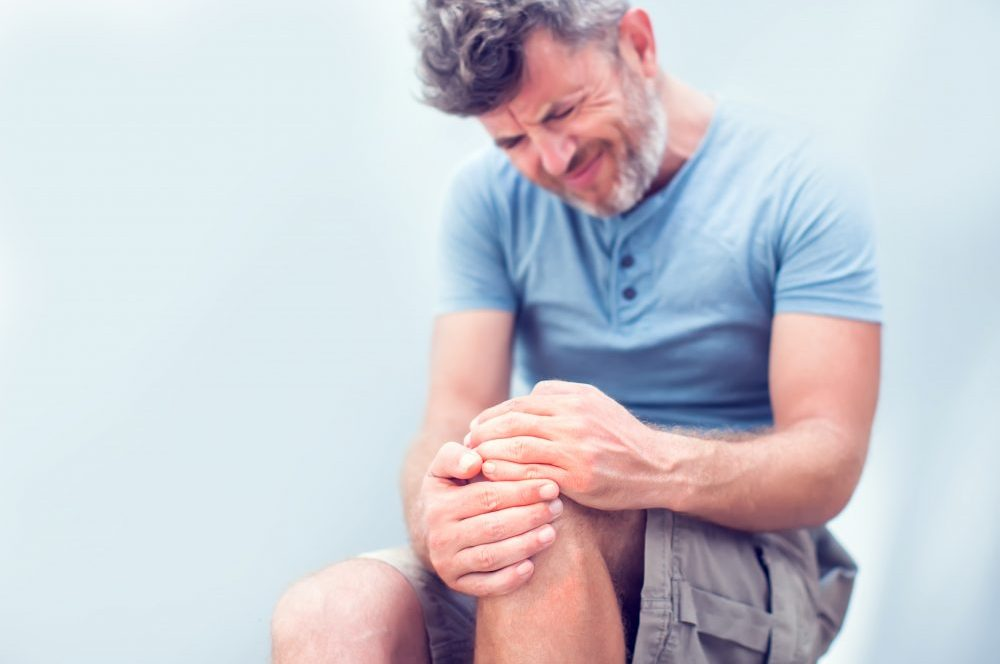 Man with knee pain close up. Pain relief concept