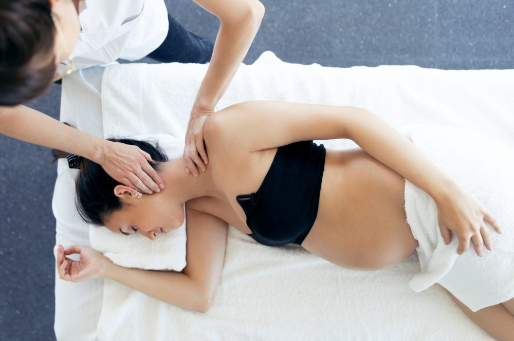 Shot of pregnant woman receiving osteopathic or chiropractic treatment in neck in a clinic.